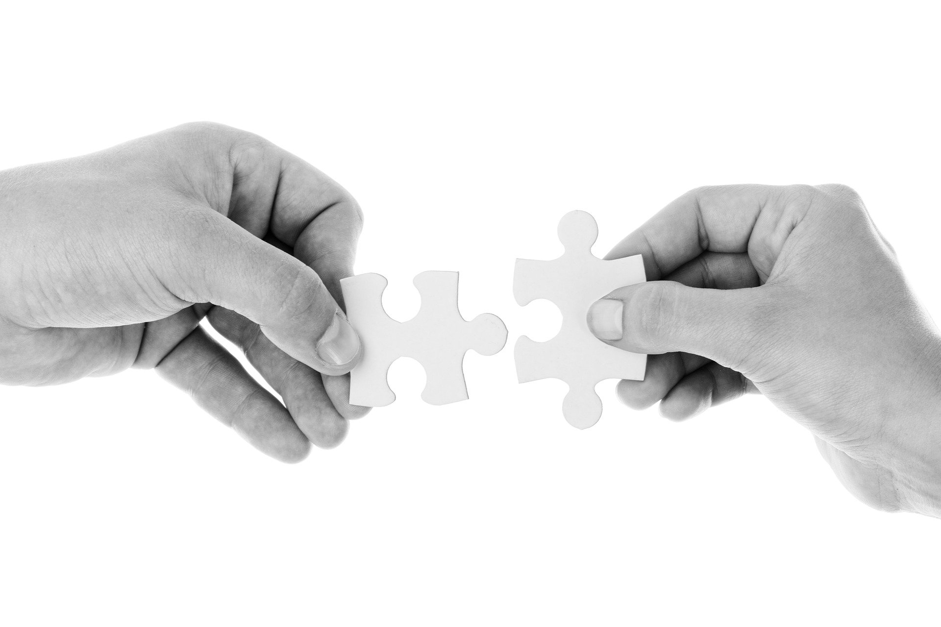 zwei Hände mit Puzzleteilen